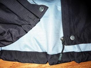 Druckknopf am Jackensaum und Wind- und Wasserschutzschutzleiste nach innen
